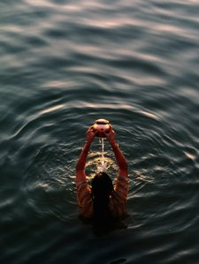 plummer-anthony-woman-pouring-water-during-morning-puja-on-ganges-varanasi-india
